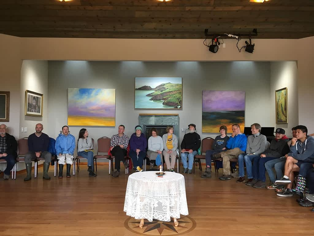 a group of people sit in a circle in a room with beautiful paintings