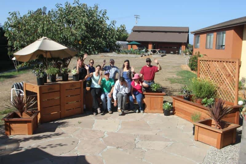 members of Camphill Communities California stand outdoors with redwood garden planters