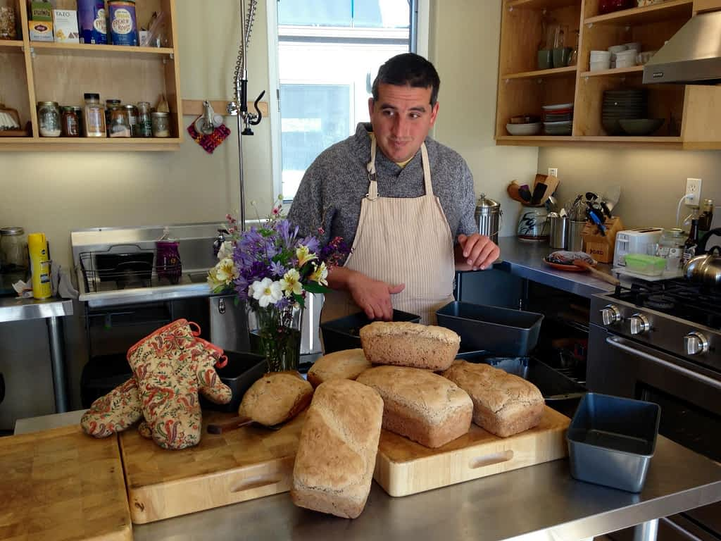 a man stands in a kitchen with six loaves of freshly baked bread