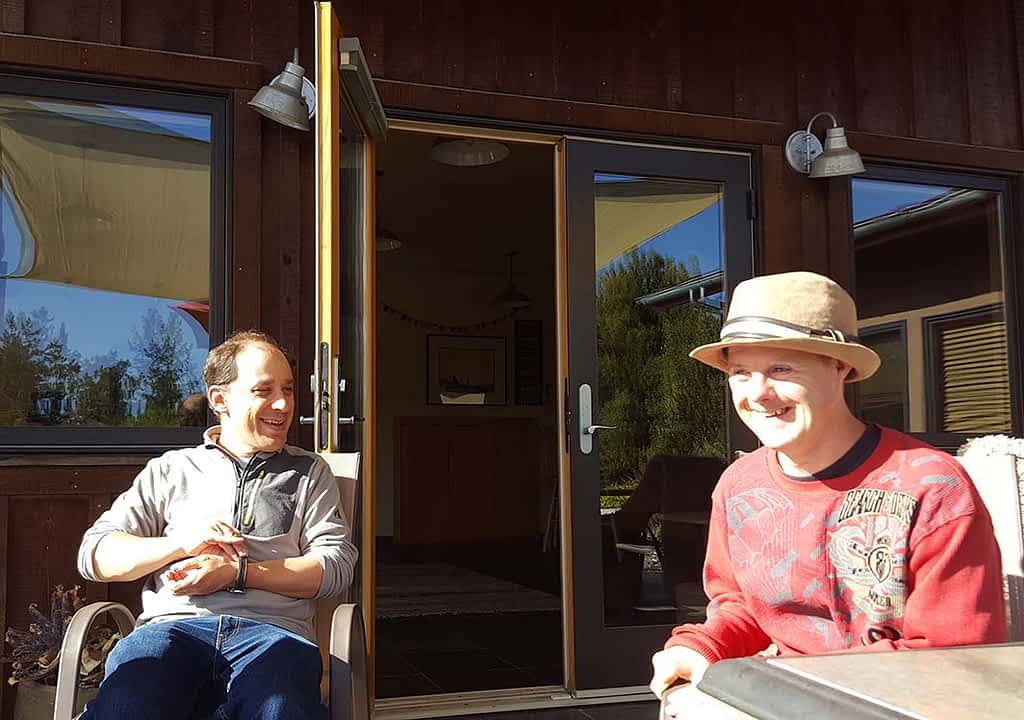 Two Camphill California residents hang out on a sunny porch laughing