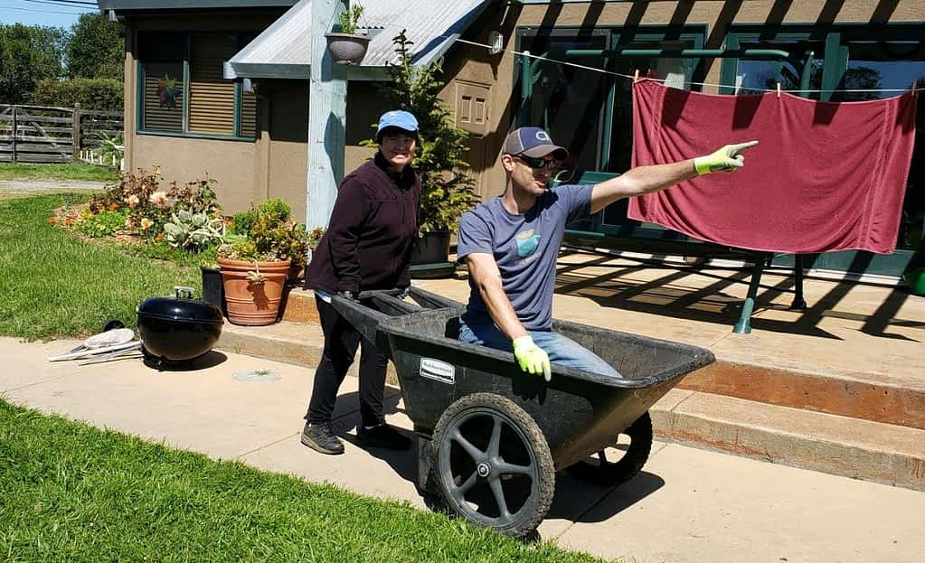 a man is playfully riding in a wheelbarrow and being pushed by a young woman