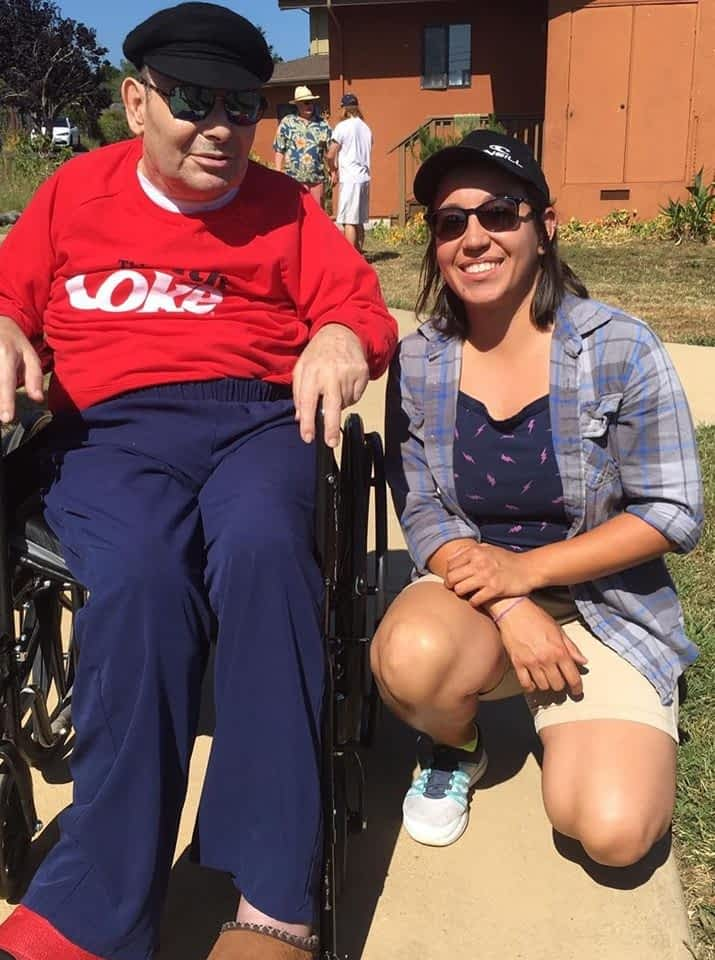 a woman poses with a man sitting in a wheel chair outdoors