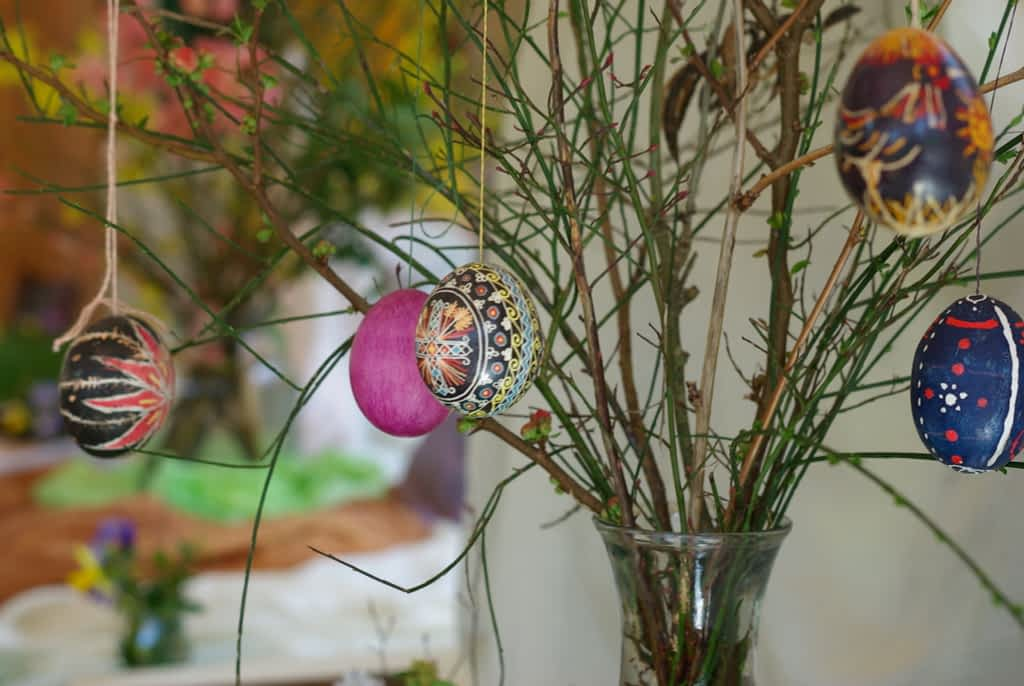 decorated egg shells hang from a branch in a vase